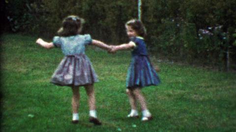 1953: Young girlfriends playing in backyard fall down tears ensue Footage