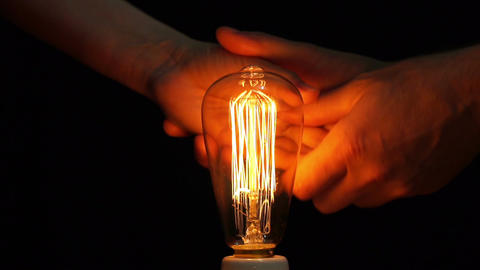 Antique Filament Bulb Man and Woman Warming Hands Footage