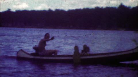 1953: Crafty man driving outboard motor rigged canoe across lake Footage