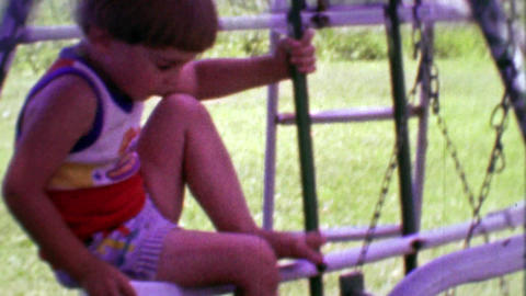 1968: Cute bowl cute boy waves from summer playground set Footage