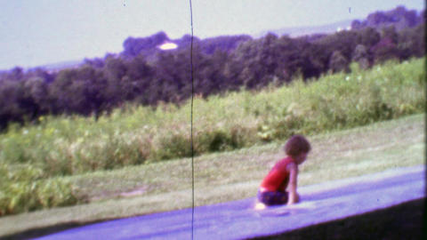 1968: Homemade slip and slide boy plays on watered tarp Footage