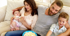 Family with pop corn on the couch Footage