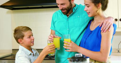 Happy family holding orange juice Footage