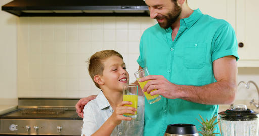 Father clink orange juice glasses with his son Footage