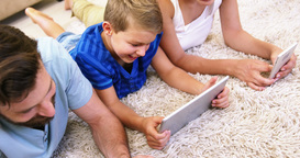 Happy family using tablet and smartphone lying on a carpet Live Action