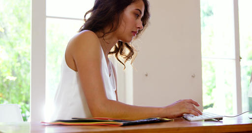 Unsmiling woman using a computer Live Action