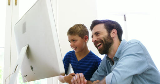 Happy father and son using computer together Live Action