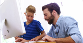 Father and son using computer together Live Action