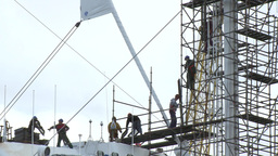 Workers assemble scaffold on a ship mast in a dry dock port Footage