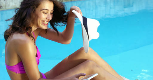 Smiling woman relaxing at the edge of pool and using smartphone Live Action