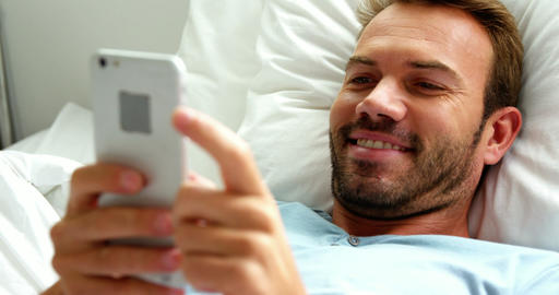 Man smiling and using smartphone on bed Live Action
