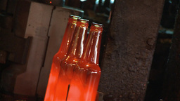 Hot Glass Being Transformed Into Glass Bottles stock footage