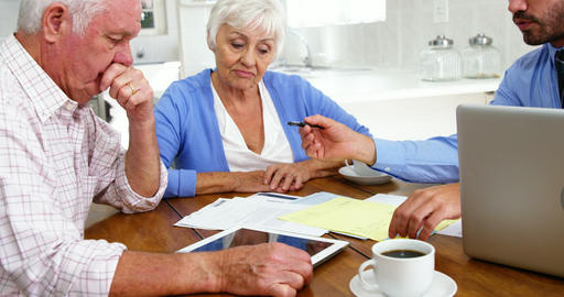 Mature couple filling some formal documents with man Live Action