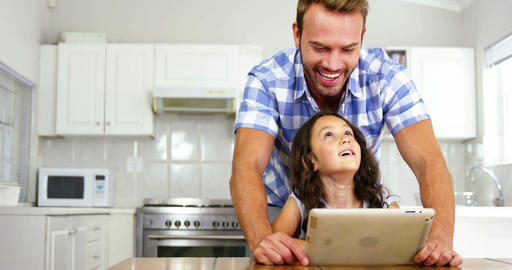 Daughter and father laughing in front of a tablet Live Action