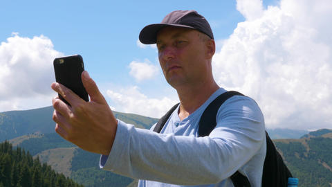 Tourist man using mobile phone for selfie photo on mountain landscape, low angle Footage
