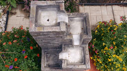 Square Stone Step Fountain Amidst Colorful Flowers Live Action