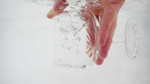 Tumbler is immersed in water, water fills glass, slow motion on white background Footage