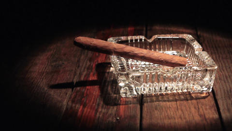 Horizontal panorama of a cigar lying in a black ashtray in the beam of light Footage