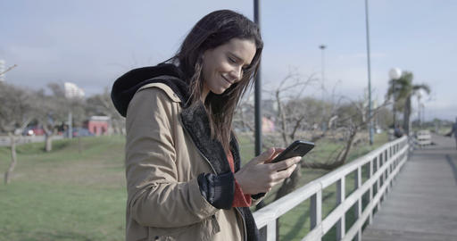 Beautiful woman browsing and texting on the phone, outdoors – 4K Live Action