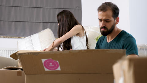 Young man and woman are unpacking in their new house Footage