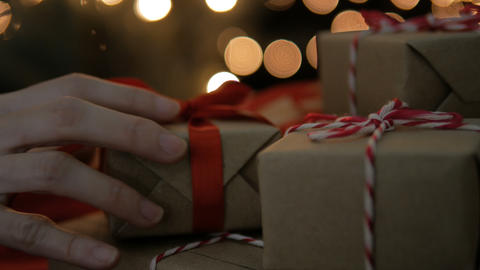 Hand of female putting Christmas gift box on bokeh lights background Footage