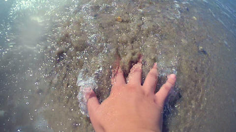 Girl's hand lies on sandy beach and sea wave is rolling close-up Footage