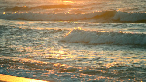 Rays of the setting or rising sun with sea waves on the shore close up Footage