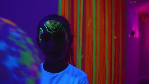 Girl with body painting on face holding balloon in dark room with fluor light Footage