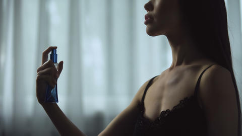 Sexy woman sensually using expensive perfumes, greatly enjoying delightful smell Live Action
