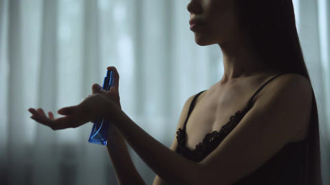 Hot seductive female applying perfumes on hands, inhaling satisfying aroma Footage