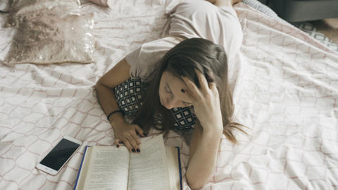 Brunette lying on the bed and reading 영상물