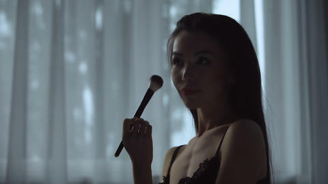 Hot woman playfully uses makeup brush on her body, making final adjustments Footage