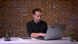 Handsome caucasian man sitting in front of the laptop and typing on it in office Footage
