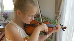 Young schoolgirl is practising playing viola. Closeup shot Footage