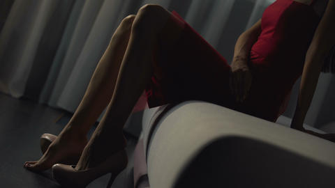 Feminine girl slowly takes off gorgeous shoes on a bedroom sofa, bare feet Live Action