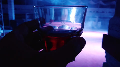 Hand with a glass is going to drink an alcoholic drink in... Stock Video Footage