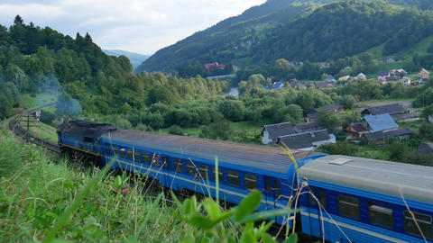 A blue train travels in the Carpathians past the village. Summer Footage