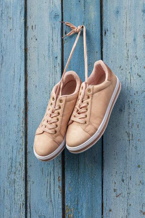pair of beige female sports shoes hanging フォト
