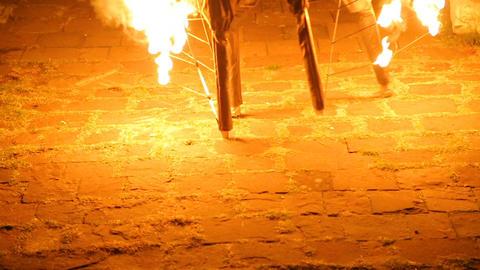 Man performing strange dance on flaming stilts, night street performance culture Footage