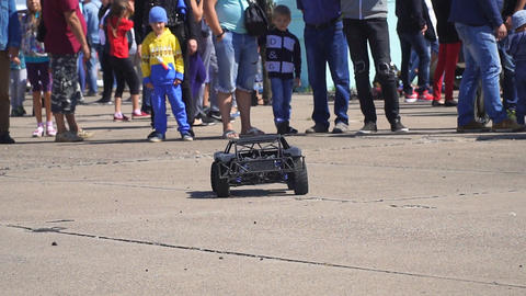 Black radio-controlled model of a car drives fast in the park Footage