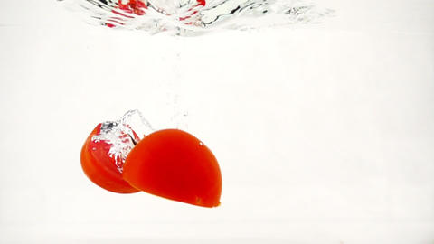 Juicy tomatoes halves are immersed in water with splashes and bubbles, slow Footage