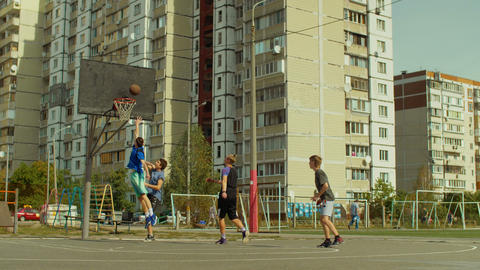 Teen streetball players playing basketball game Footage