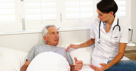 Nurse taking care of mature man lying on a bed Live Action
