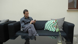 Man with Smartphone and Sitting on Couch Footage