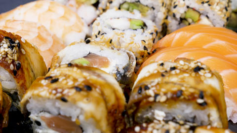 Sushi rolls in variety mix on black stone plate Footage