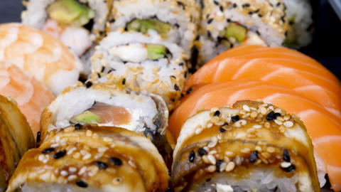Sushi rolls in variety mix on black stone plate Live Action