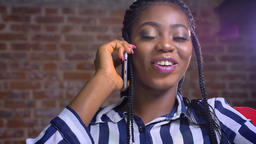 african female close-up at her workplace sitting and talking over smartphone Footage