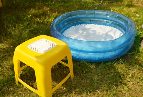 Children's inflatable pool and a small chair stand on the green grass on a Sunny Photo