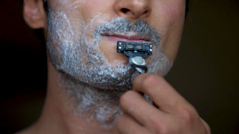 Face of the man during shaving Beard is processed by foam for shaving Hair on GIF