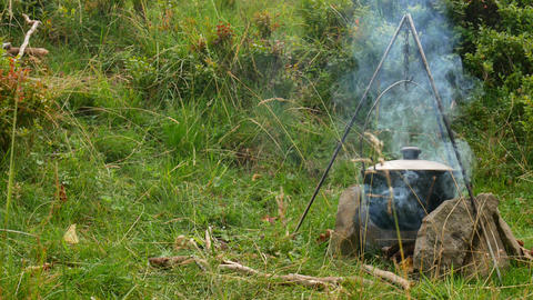 Cooking outdoor food in tourist pot at bonfire. Process preparing camping food Live Action
